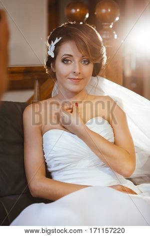 Pre-wedding preparation. Fiancee sitting on sofa and smiling. Bride wearing white wedding dress and veil. Indoor