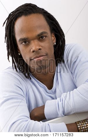 Stylish African American man with dreadlocks isolated on white.