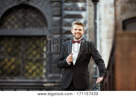 Wedding photo shooting. Bridegroom standing outdoor and smiling. Man wearing white shirt, black jacket and bow-knot. Waist up, looking at camera