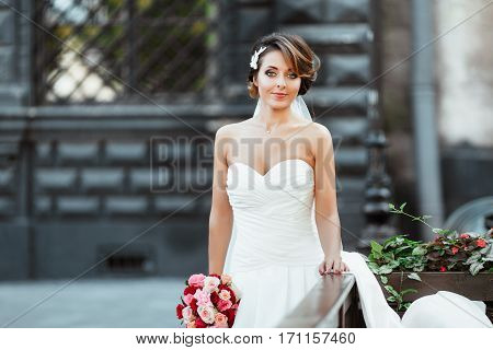 Wedding photo shooting. Bride standing with bouquet. Woman wearing white dress and veil. Looking at camera, nice hairdo and make-up. Outdoor