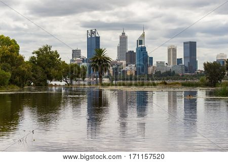 The Perth city skyline is reflected in a pond on the South Perth foreshore during an overcast day. Western Australia, Australia. February 13, 2017.