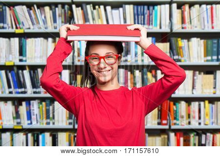 Smiling teen student in a library