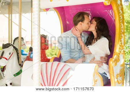 Joyful couple kissing on a carousel