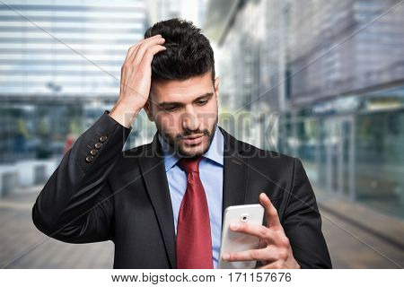 Portrait of a worried man looking at his mobile phone