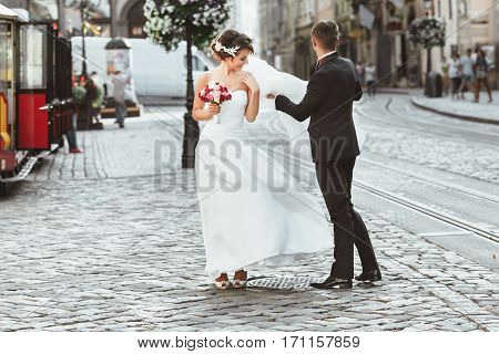 Wedding photo shooting. Bride and bridegroom walking in the city. Husband holding his wife's veil. Outdoor, full body