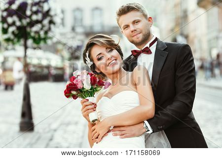 Wedding photo shooting. Bride and bridegroom in the city. Man embracing girl's waist from back. Holding bouquet and smiling. Outdoor, waist up