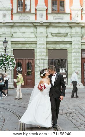 Wedding photo shooting. Bride and bridegroom in the city. Married couple kissing and holding bouquet. Outdoor, full body, mock-up