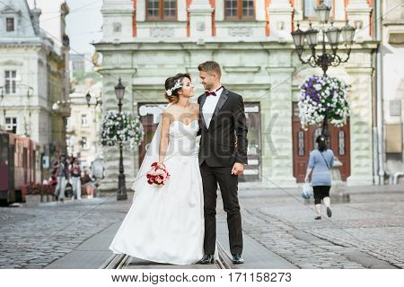 Wedding photo shooting. Bride and bridegroom walking in the city. Married couple embracing and looking at each other. Outdoor, full body