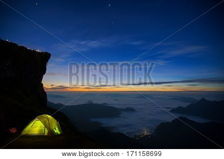 mountain and cliff with fog on sunrise at phucheefah chiang rai province thailand with Small Camping Tent Illuminated Inside. Night Hours Campsite. star space galaxy Recreation and Outdoor Photo Collection.