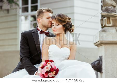 Wedding photo shooting. Bride and groom sitting near monument. Holding bouquet, both with closed eyes. Bridegroom kissing bride's forehead. Outdoor, waist up, closeup