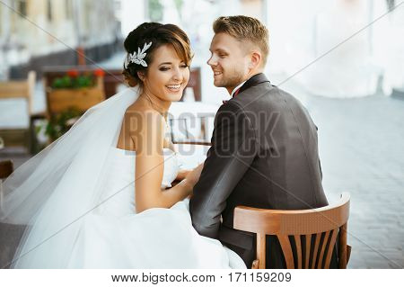 Wedding photo shooting. Bride and bridegroom sitting on chairs in cafe and smiling. Outdoor, rear view