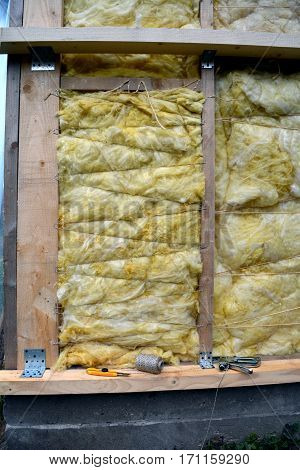 house wall with insulation material rockwool fragment and tools