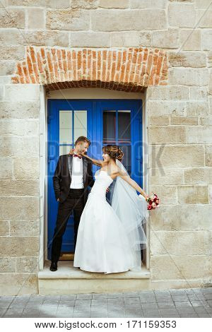 Bride and bridegroom standing near blue door, looking at each other and smiling. Leaning back from each other, embracing with one hand. Outdoor, full body, profile