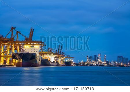 Container Cargo freight ship with working crane loading bridge in shipyard at dusk for Logistic Import Export background transportation logistic business and delivery concept.