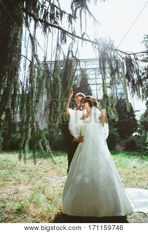 Wedding photo shooting. Bride and bridegroom standing under pine tree. Woman holding branches and man embracing her. Outdoor, full body