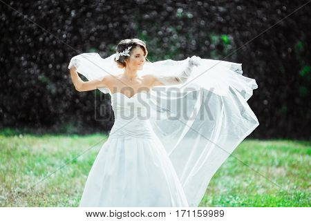 Wedding photo shooting. Bride under rain, holding her veil. Looking aside. Wearing white dress and long veil. Outdoor
