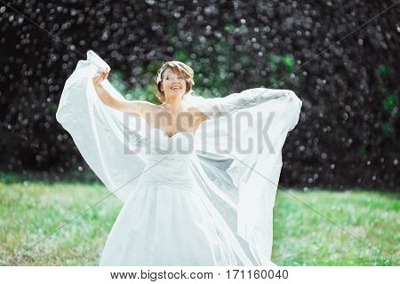 Wedding photo shooting. Bride under rain, smiling and holding her fluttering veil. Looking up. Wearing white dress and long veil. Outdoor