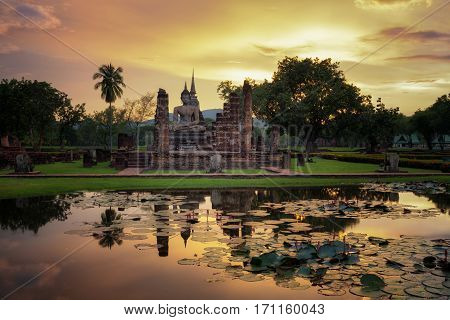 Buddha Statue at Wat Mahathat in Sukhothai Historical Park and water lilly in the poolThailand