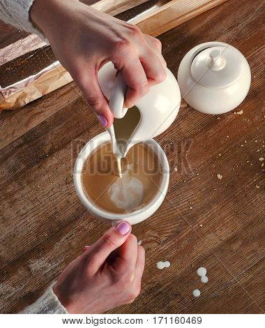 Woman Pouring Milk To A Cup Of Espresso Coffee.