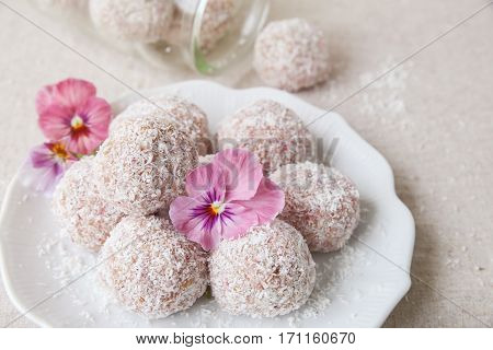 Homemade strawberry date cashew and coconut bliss ball with edible flowers