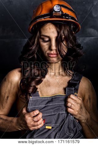 close-up portrait sexy female miner worker in coveralls over his naked body, helmet on the head with a flashlight.