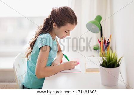 people, children, education and learning concept - happy girl with book writing to notebook at home