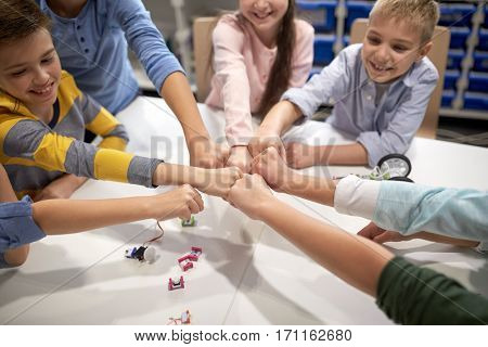 education, children, technology, science and people concept - group of happy kids building robots at robotics lesson and making fist bump