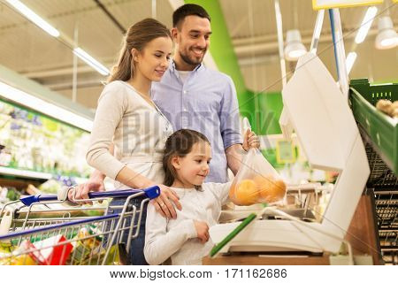 shopping, sale, consumerism and people concept - happy family with child weighing oranges on scale at grocery store
