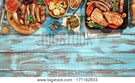 Variety of grilled food on the blue wooden table on a sunny day grilled steak grilled sausage and grilled vegetables. Top view. Outdoors Food Concept