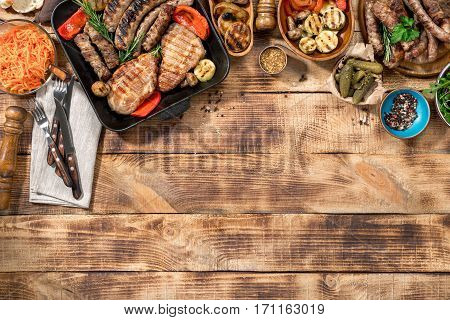 Different foods cooked on the grill on the wooden table with copy space grilled steak grilled sausage and grilled vegetables. Top view
