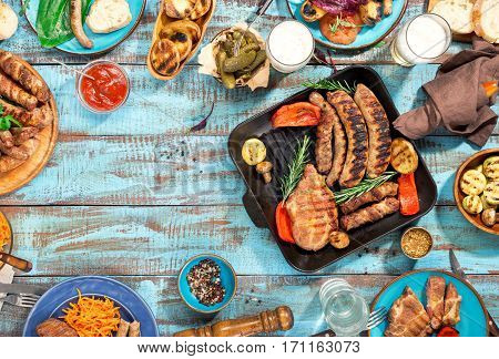 Frame of different food cooked on the grill on the blue wooden table on a sunny day grilled steak grilled sausage grilled vegetables and lager beer. Top view. Outdoors Food Concept