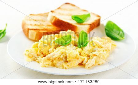 Scrambled Eggs And Toasts With Basil.