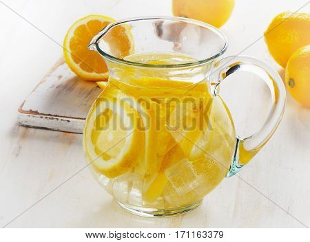 Water With Lemon And Ice In A Glass Jug.