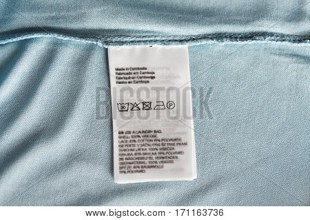 clothes, laundry and housekeeping concept - label with users manual of clothing item