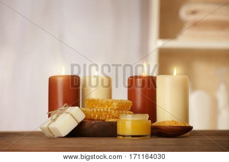 Spa concept. Beautiful composition of alight candles and natural honey treatments on wooden table