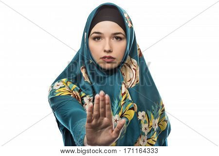 Female wearing a hijab conservative fashion for muslims middle east and eastern european culture. She is isolated on a white background and holding hands up in stop gesture