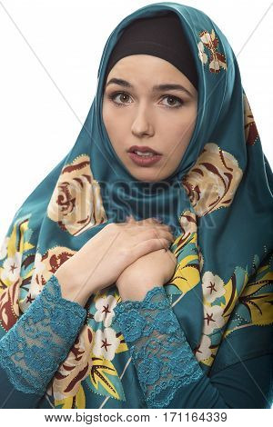 Female wearing a hijab conservative fashion for muslims middle east and eastern european culture. She is isolated on a white background and looking scared
