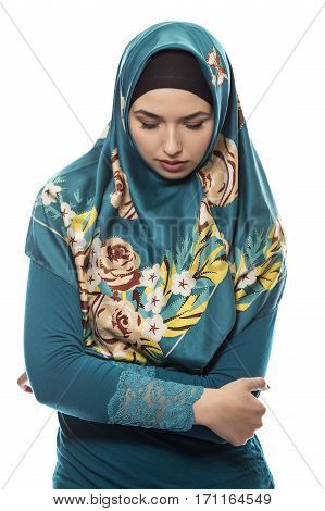 Female wearing a hijab conservative fashion for muslims middle east and eastern european culture. She is isolated on a white background and looking down because she is upset at failure