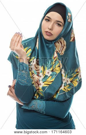 Female wearing a hijab conservative fashion for muslims middle east and eastern european culture. She is isolated on a white background and showing money gesture