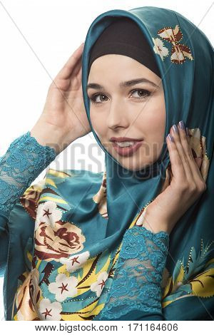 Female wearing a hijab conservative fashion for muslims middle east and eastern european culture. She is isolated on a white background and looking happy and joyful