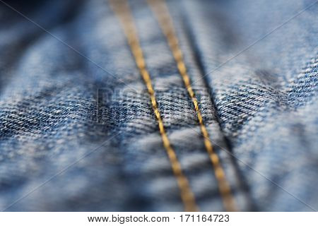 clothes, wear and fashion concept - close up of stitching on denim or jeans