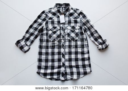 clothes, fashion and objects concept - checkered shirt with price tag on white background