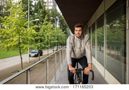 lifestyle, transport and people concept - young man riding bicycle on city street