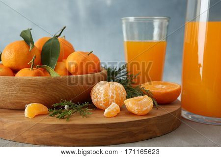 Tangerine juice in jug with fruits on table