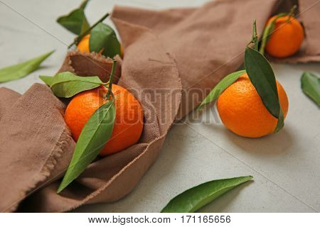 Juicy tangerines with sackcloth on grey background
