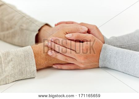 old age, support, charity, care and people concept - close up of senior man and young woman holding hands