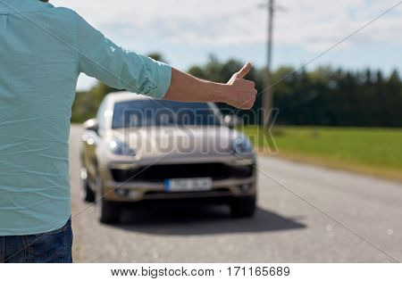 road trip, travel, gesture and people concept - man hitchhiking and stopping car with thumbs up gesture at countryside