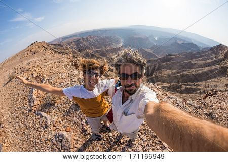Couple taking selfie at the Fish River Canyon scenic travel destination in Southern Namibia. Fisheye view from above in backlight.