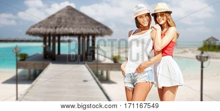 summer holidays, vacation, travel and people concept - smiling young women in hats and casual clothes over exotic tropical beach with bungalow shed background