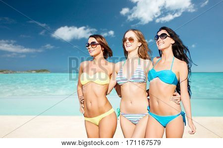 summer holidays, travel, people and vacation concept - happy young women in bikinis and shades over exotic tropical beach background